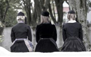 Annríki - Þjóðbúningar og skart. Þrjár stúlkur sitja á vegg. Uppáklæddar í 19. og 20 aldar peysuföt.