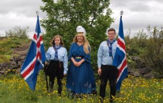 Annríki - Þjóðbúningar og skart. Fjallkonan Katrín, uppá búin kyrtli. Skátar standa sitthvoru megin við með íslenska fána.