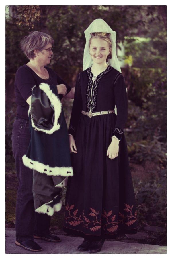 Stúlka í skautbúningi fær aðstoð við að klæðast